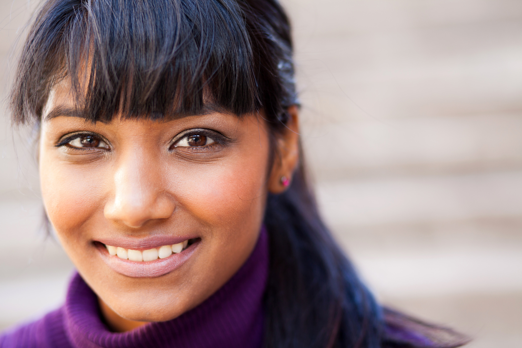 indian woman black hair purple sweater smiling