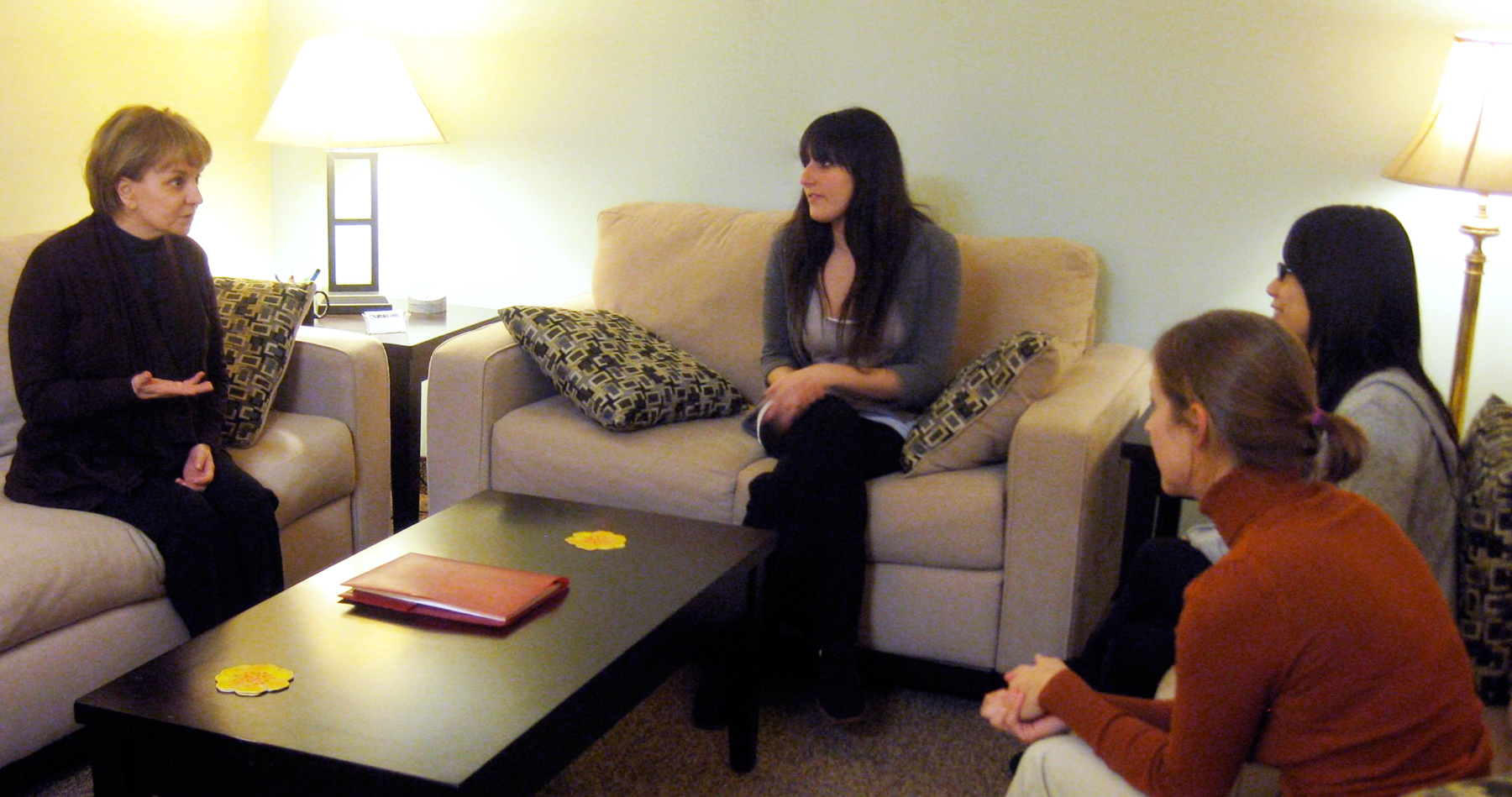 Therapist and three women in a warm and comfortable room with lamps, couches and coffee table