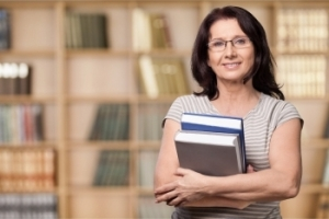 middle-aged, dark-haired woman in glasses cradling 2 textbooks