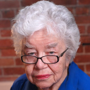 Jean Ledwith King white hair, black glasses, blue shirt, brick wall in background