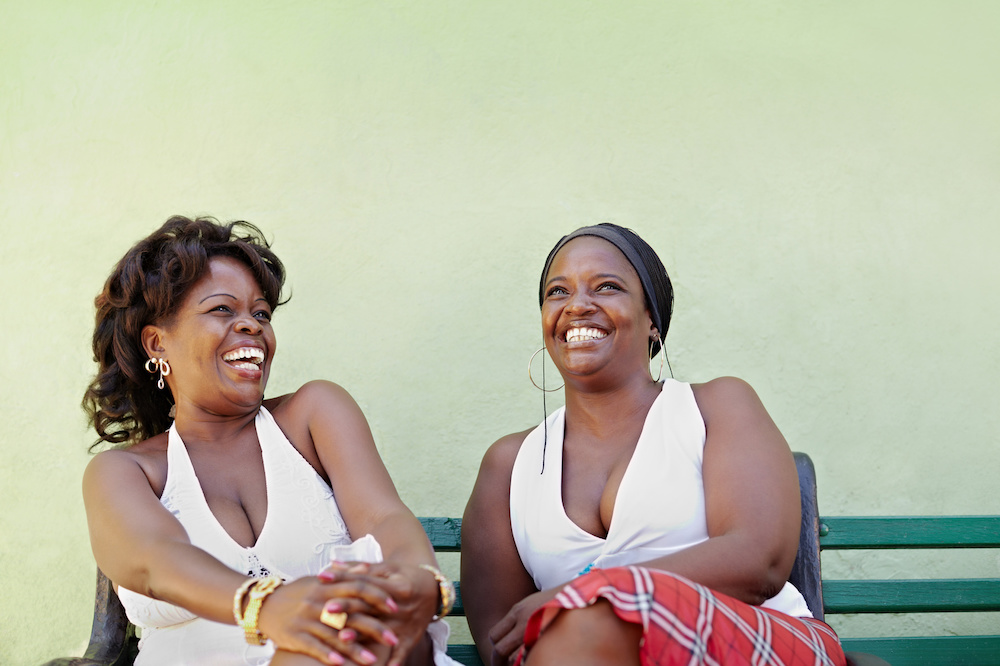 portrait of two happy african adult women talking on bench and smiling. Horizontal shape, copy space